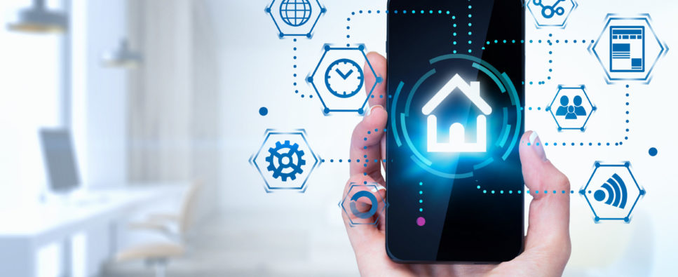 Hand of woman holding smartphone with glowing smart home interface over blurred home office background. Concept of IOT. Toned image double exposure